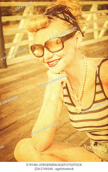 Charming portrait from the past of a smiling sunbathing pinup gal on nostalgic promenade