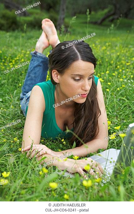 Young woman lying in meadow with laptop