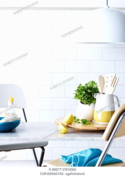 Kitchen table with utensils, sliced lemon and herbs