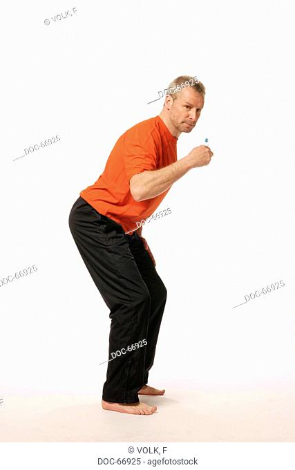 older man holding a toothbrush in his hand and standing in crouch position like doing ski-run - looking at camera exercise fŸr spinal extensor