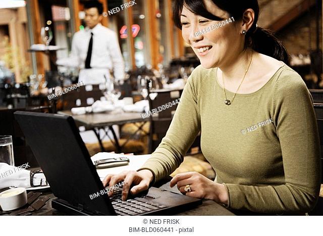 Asian businesswoman typing on laptop