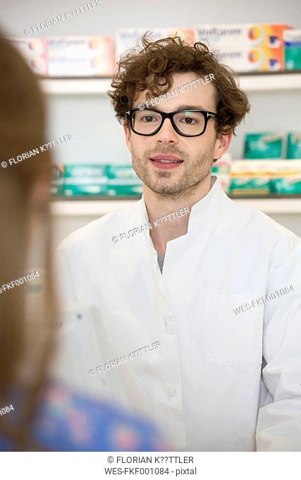 Portrait of pharmacist advising female customer