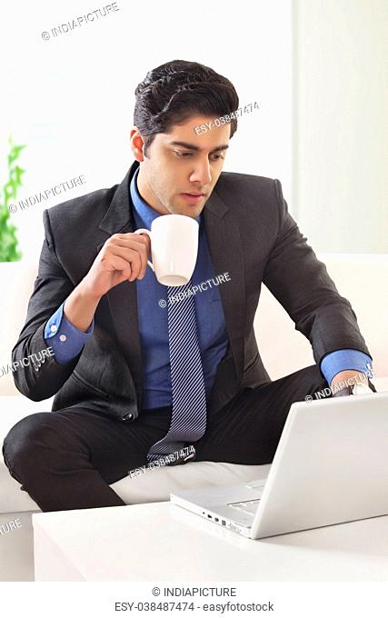 Young businessman holding a coffee cup and using a laptop