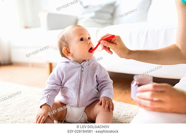 family, food, child, eating and parenthood concept - mother with puree and spoon feeding little baby at home