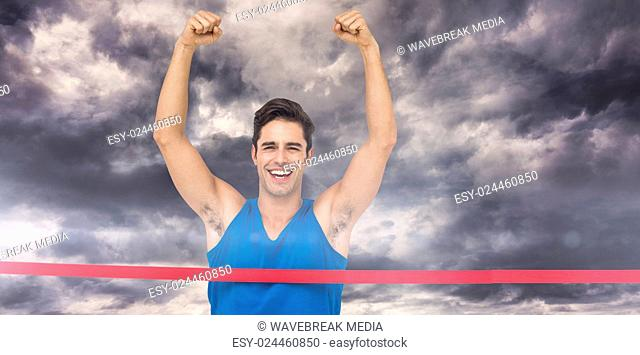 Composite image of portrait of cheerful winner athlete crossing finish line