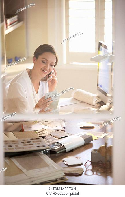 Interior designer examining swatches and talking on cell phone in home office