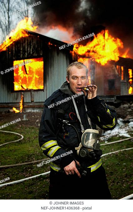 Fire fighter smoking cigarette in front of burning building