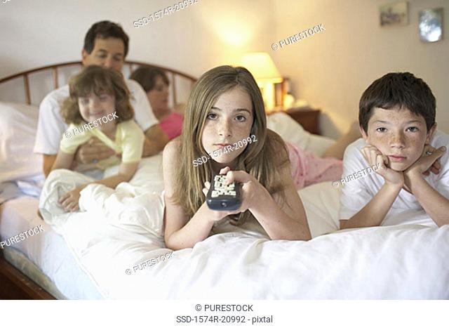 Close-up of a teenage girl and her brother lying in the bed watching TV