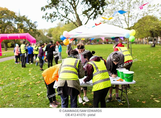 Volunteers checking runners in at charity run in park