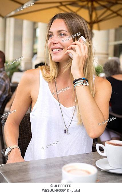 Young woman in a street cafe on cell phone looking around