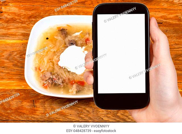 travel concept - tourist photographs of russian cabbage soup with stewed sauerkraut and sour cream in ceramic bowl on smartphone with cut out screen with blank...