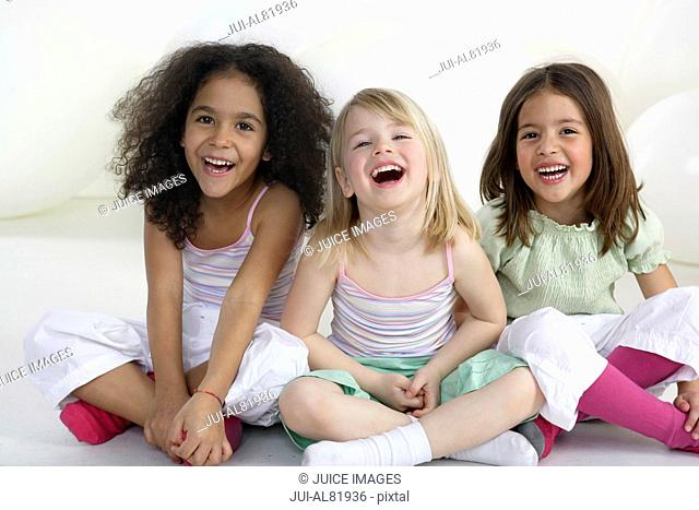 Three young girls laughing indoors