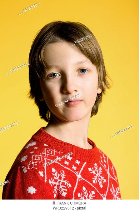 Portrait of a Boy with Blond Hair in Red Christmas Sweater