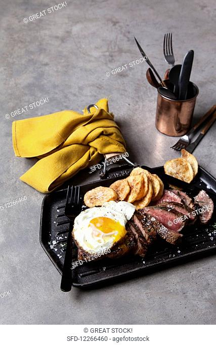 Beef steak with fried egg and potato chips