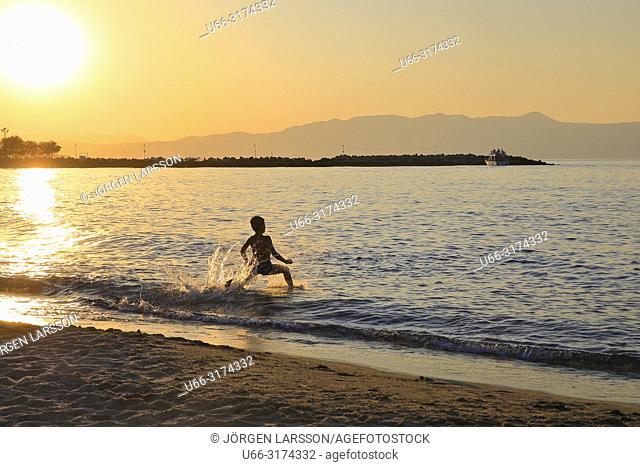 Silhouette of boy on the beach. Platanias. Crete, Greece