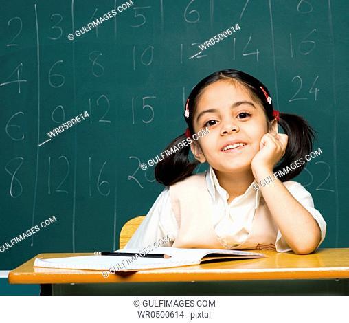 Girl 6-7 sitting on desk, smiling, portrait
