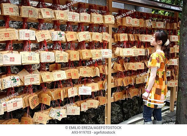 Kiyomizu-dera temple. Kyoto, Kansai, Japan. Woman looking at 'ema' prayer boards in a Shinto shrine