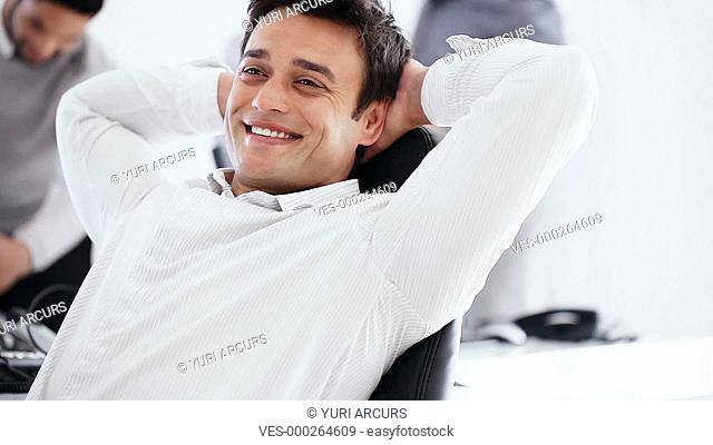 Happy young businessman leaning back on his chair with his arms behind his head and smiling at the camera