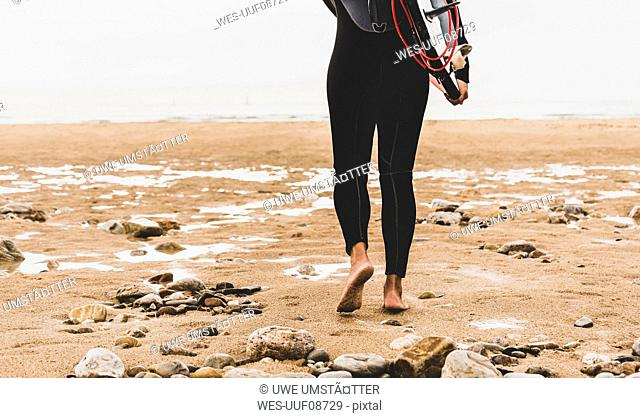 France, Bretagne, Crozon peninsula, woman walking on beach carrying surfboard