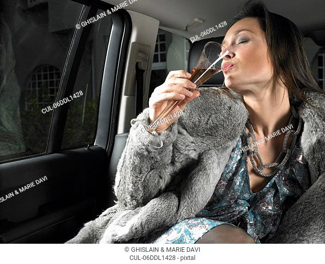 Woman in car, drinking and celebrating