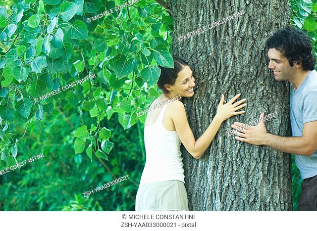 Couple looking at each other from around tree