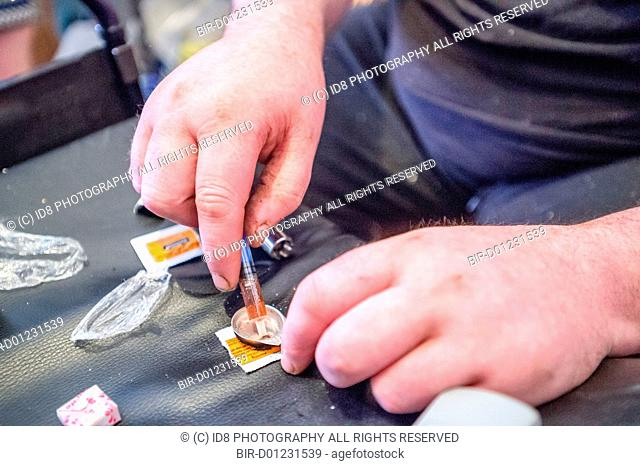 Preparing heroin ready for injecting using a wheel chair for a table