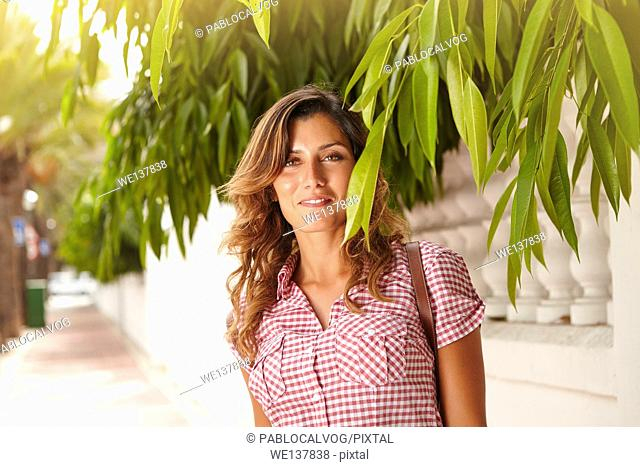 Caucasian lady in brightly lit day smiling at the camera through green branches