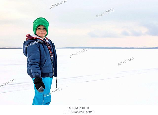 A young boy walking on a frozen lake while ice fishing during a winter family outing; Wabamun, Alberta, Canada