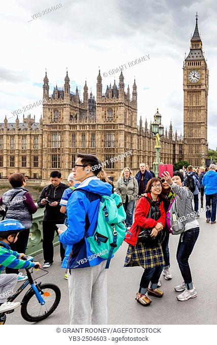 Young Tourists Pose For Selfies In Front Of Big Ben and The Houses Of Parliament, Westminster Bridge, London, England