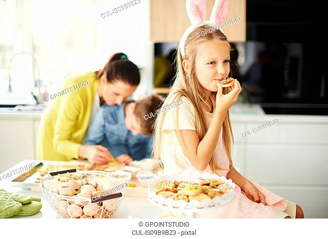 Girl eating easter biscuits on kitchen counter