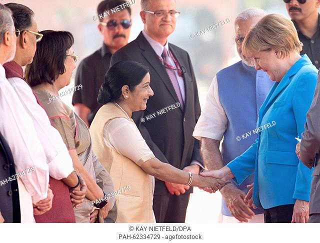 German Chancellor Angela Merkel is greeted by members of the Indian government next to Prime Minister Narendra Modi (behind Merkel) in New Dehli, India