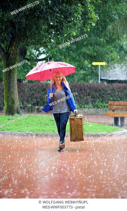 Austria, Thalgau, teenage girl with red umbrella walking in the rain with suitcase