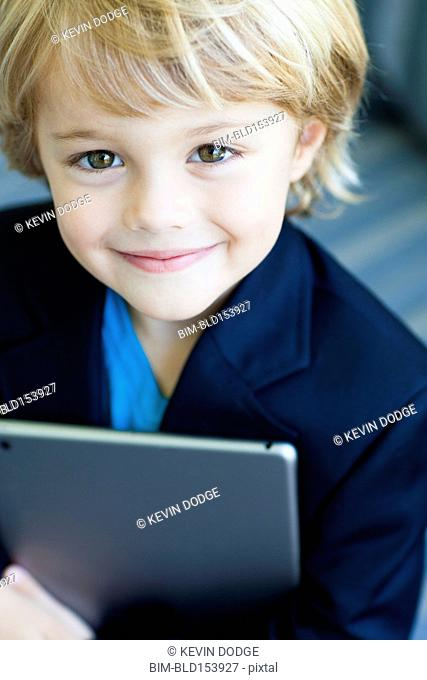 Smiling Caucasian boy in business suit holding digital tablet