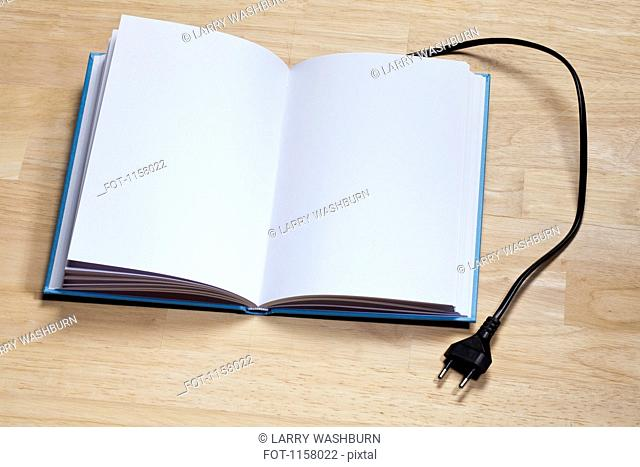 A hardcover book with an electric plug attached to it