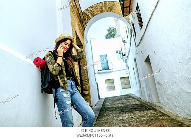 Young traveling woman talking on cell phone in a town