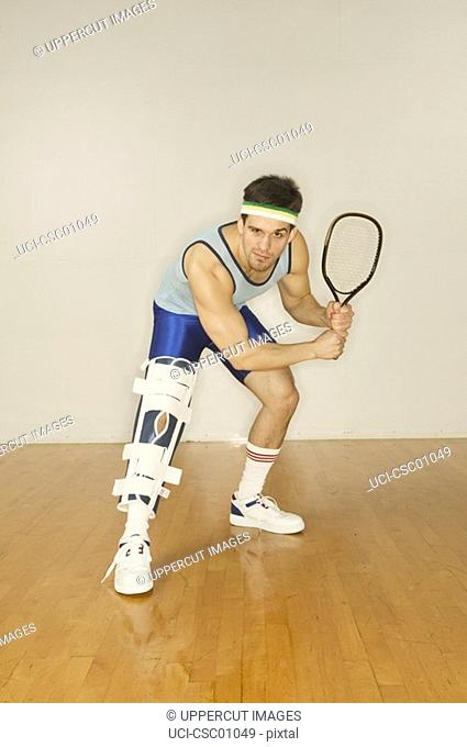 Man in leg brace holding racquetball racket