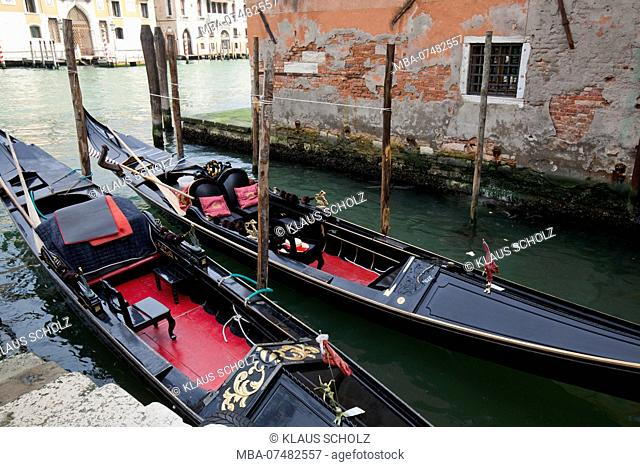 two black gondolas lie in narrow canal in Venice