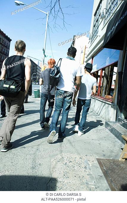Young men walking NE along sidewalk on 8th Avenue in Chelsea, New York City, rear view