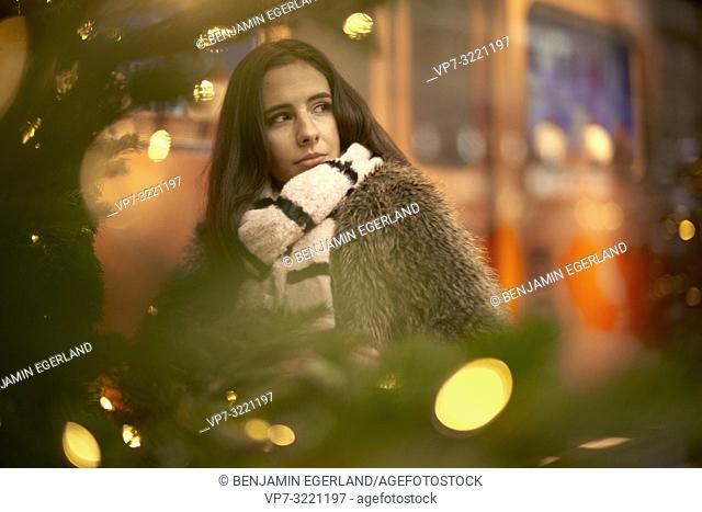 portrait of woman behind lights of christmas tree, wearing fashionable winter clothes and scarf, in city Munich, Germany