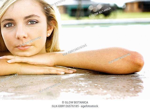 Portrait of a woman leaning on the ledge of a swimming pool