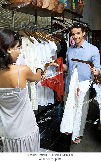 young couple choosing clothes at store