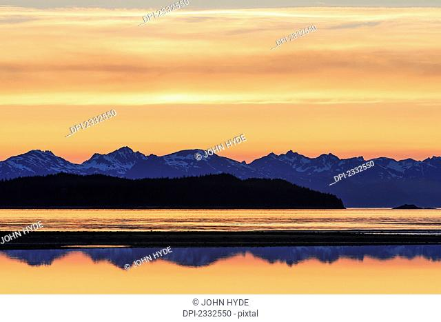 A tide pool reflects the evening sky eagle beach state recreation area with the chilkat mountains and lynn canal in the distance;Alaska united states of america