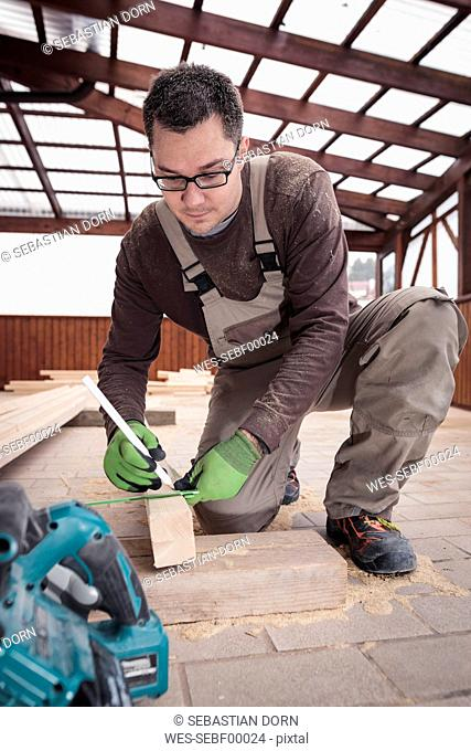 Roof insulation, worker sawing woodbar