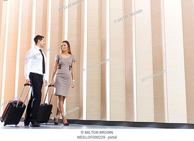 Businessman and businesswoman arriving in hotel