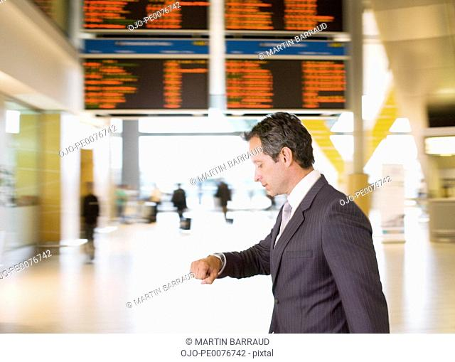 Businessman checking watch in airport