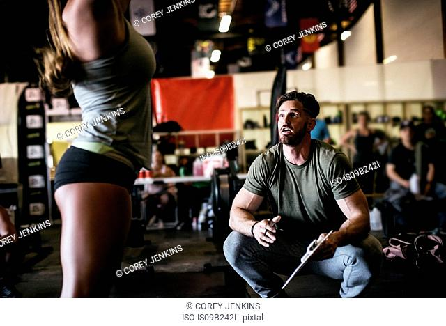 Trainer observing cross training athlete exercising in gym