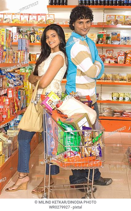Man and woman standing back to back with trolley in supermarket MR748A,748B