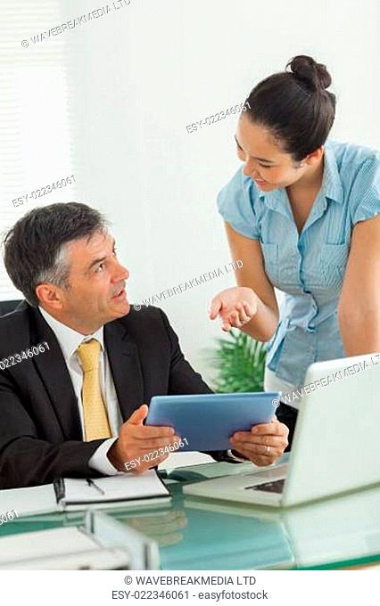 Business people working on the same digital tablet in an office