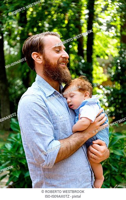 Father holding baby son, outdoors