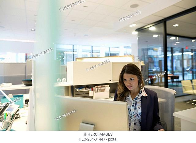 Focused young businesswoman working at computer in office